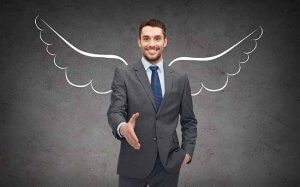 happy businessman with angel wings over gray