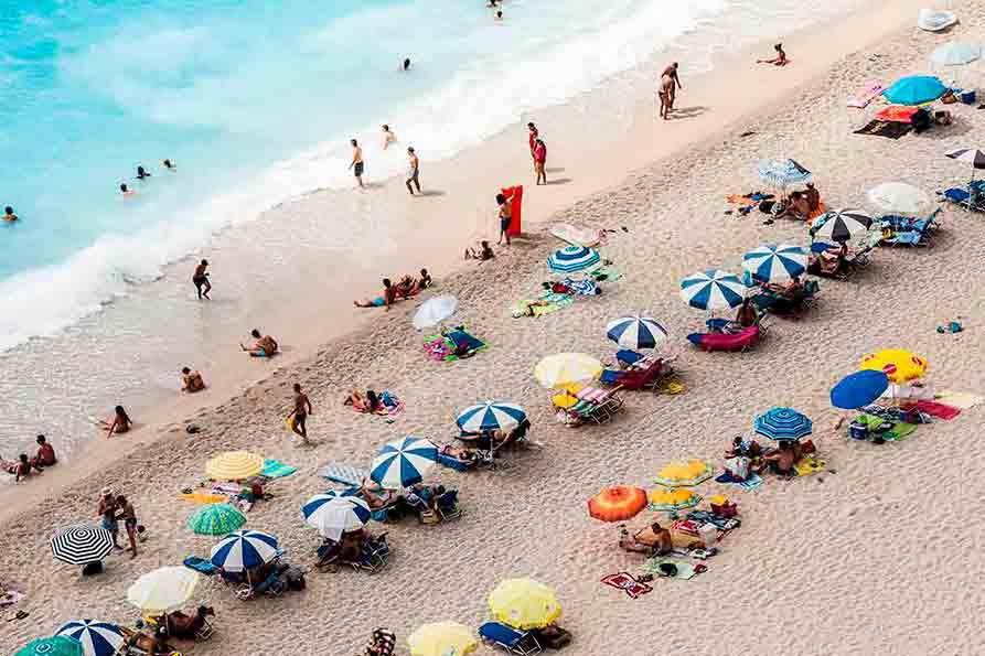 Turistas en la playa postcovid.